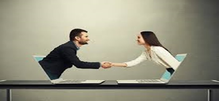 A man and woman coming out of laptops shaking hands